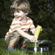 Young boy playing at home near house in garden with various toys — Stock Photo