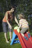Young boy playing at home near house in garden with his mother with various toys — Stock Photo