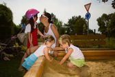 Family enjoying day on sandpit — Foto de Stock