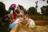 Family enjoying day on sandpit — Photo