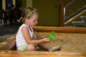 Little girl playing on sandpit — Stock Photo