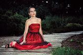 庭でポーズをとって赤いドレスの女 — ストック写真