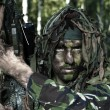 Hidden special forces soldier with sniper rifle observing terrain in natural forest scenery — Photo #30726757