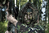 Hidden special forces soldier with sniper rifle observing terrain in natural forest scenery — Stock Photo