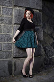 Beauty in green skirt enjoying photo shoot with stone wall — Stockfoto