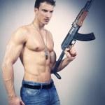 Power muscle man with AK-47 gun — Stock Photo