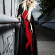 Stock Photo: Blonde girl posing in black cloak
