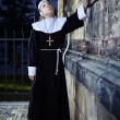 Stock Photo: Nun touching church wall