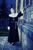 Nice nun touching church wall — Stock Photo
