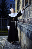 Nun touching church wall — Stock Photo