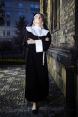 Nun looking to skies nearby church — Stock Photo