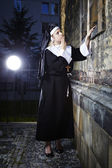 Young nun looking to church — Stock Photo