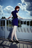 Redhead in blue posing in summer light on floodgate — Stock Photo