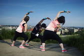 Three fitness people exercising in city — Stock Photo