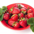 Strawberry with leaves on red plate  — Stock Photo