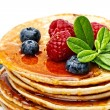 Small pancakes topped with honey, raspberries and bilberries - Stok fotoğraf