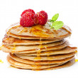 Small pancakes topped with honey, raspberries and mint - Stock Photo