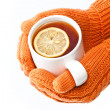 Hands in orange knitted mittens holding a cup of tea with lemon - Stock Photo