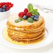 Pile of  pancakes topped with honey, raspberries and bilberries — Stock Photo