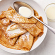 Sweet pancakes on plate with condensed milk — Stock Photo #24481143