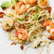 Spaghetti with prawns, sea scallops and basil - Stock Photo