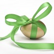 Golden Easter egg tied by green ribbon on white background — Stock Photo #24481643
