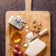 Cheese with honey, nuts and grapes on wooden cutting Board — Stock Photo #24482047