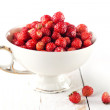 Wild strawberries in graceful white cup on white wooden backgrou — Stock Photo #24482077
