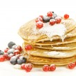 Small pancakes topped with honey, red currants and bilberries — Stock Photo