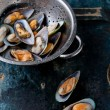 Raw washed mussels in colander - Stock Photo