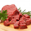 Raw fresh beef cubes on board with greens — Stock Photo