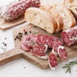 Italian salami with bread on wooden cutting Board - Stock Photo
