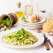 Pasta with pesto on white plate - Stock Photo
