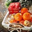 Mandarins in basket with Gift and Christmas tree branch — Stock Photo