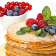 Pile of  pancakes topped with honey, raspberries and bilberries - Stock Photo