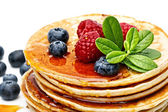 Small pancakes topped with honey, raspberries and bilberries — Stock Photo