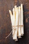 Raw white asparagus on wooden table — Stock Photo