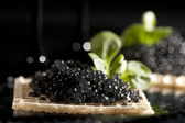 Sandwiches with black caviar on black background — Stock Photo