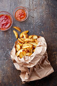 "Fried potato ""country-style"" in kraft bag — Stock Photo"