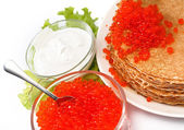 Served place setting: pancake with red caviar, sour cream and greens — Stock Photo