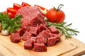 Raw fresh meat sliced in cubes on board with vegetables — Stok fotoğraf