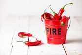 Red chili peppers in fire bucket — Stock Photo