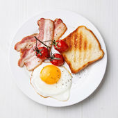 Breakfast with Fried egg and bacon on plate — Stok fotoğraf