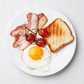 Frukost med stekt ägg och bacon på tallrik — Stockfoto
