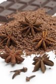 Anise stars, grated chocolate and chocolate plate — Stock Photo