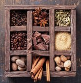 Assortment of spices and coffee beans in wooden box — Stock Photo