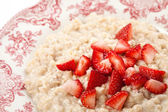Bowl of porridge with strawberry — Stock Photo