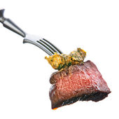 Piece of beef steak with herb butter on fork on white backgroun — Stock Photo