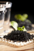 Served place setting: vodka and sandwiches with black caviar on — Stock Photo