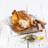 Whole roasted chicken on white wooden background — Stock Photo